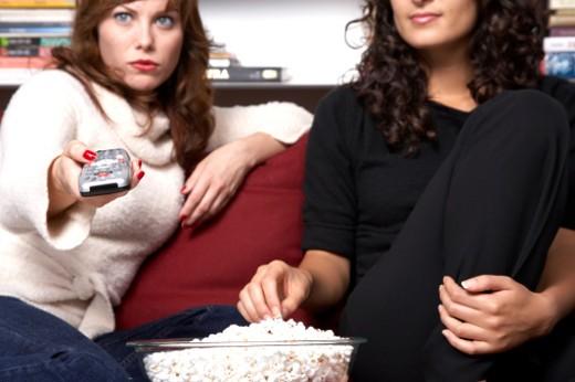Two women watching TV, eating popcorn : Stock Photo