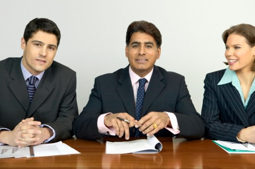 Portrait of Three Businesspeople Sitting in a Line at an Interview : Stock Photo