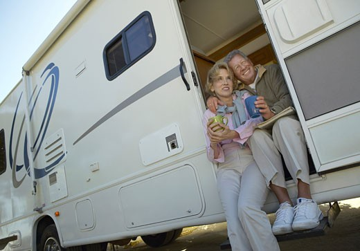Senior Couple Sit Side by Side in the Doorway of Their Motor Home, Holding Mugs and Smiling : Stock Photo