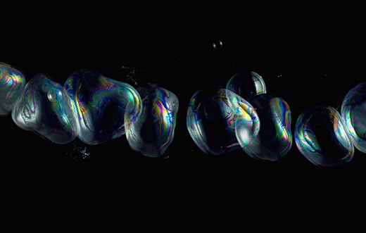 Soap bubbles in a row on black background. : Stock Photo