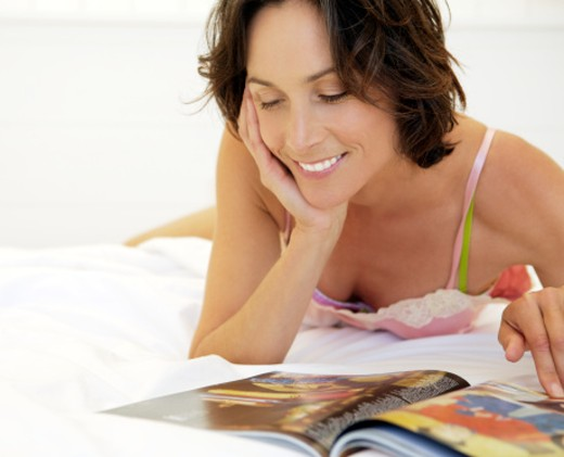 Stock Photo: 1598R-9948772 Woman lying on bed, reading magazine, smiling