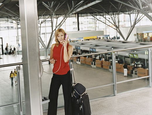 Stock Photo: 1598R-9948784 Business Woman using a Pay Phone in an Airport