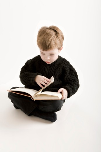Boy (2-4) reading book, close-up : Stock Photo