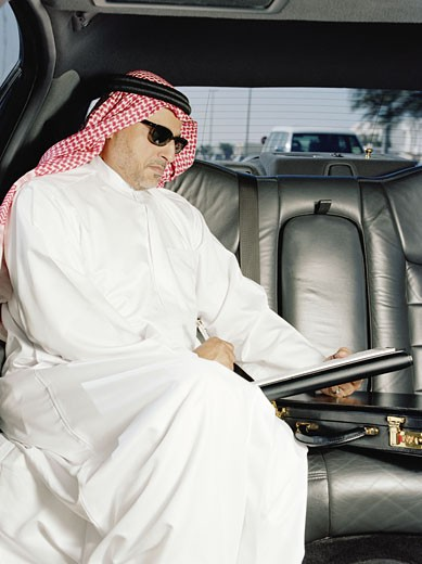 Man in traditional Arabic clothing in car, reading : Stock Photo