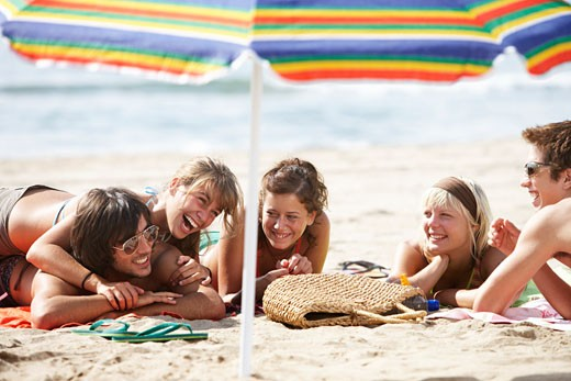 Group of friends lying on beach, laughing, umbrella in foreground : Stock Photo