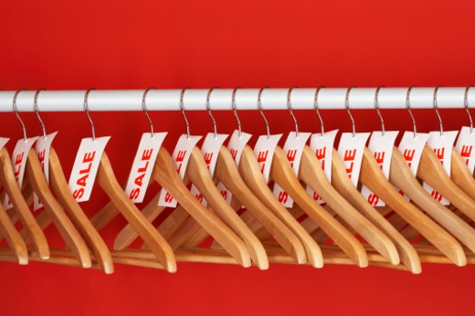 Rail of clothes hangers with sale tags attached,against red background : Stock Photo
