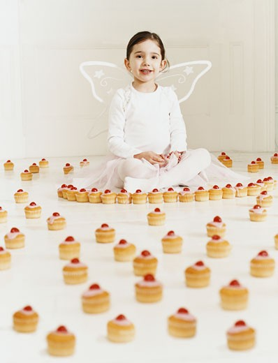 Young Girl Dressed as a Fairy Sitting Amongst a Large Selection of Cup Cakes : Stock Photo