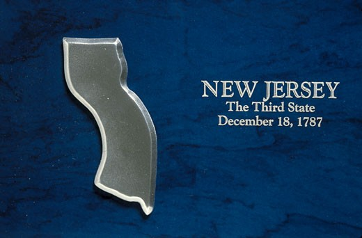 Stock Photo: 1598R-9949567 'This is a silver map of the state of New Jersey against a blue background. It says, New Jersey, The Third State, December 18, 1787, which is the date it entered the Union.'