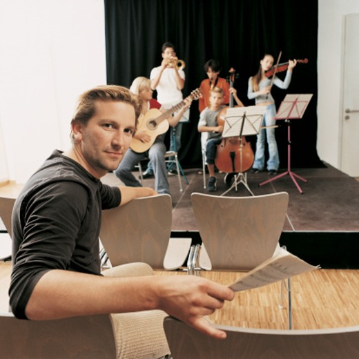 Music Teacher Sits in a Chair With a School Band Rehearsing on a Stage : Stock Photo