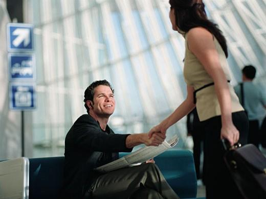 Man greeting woman at airport : Stock Photo