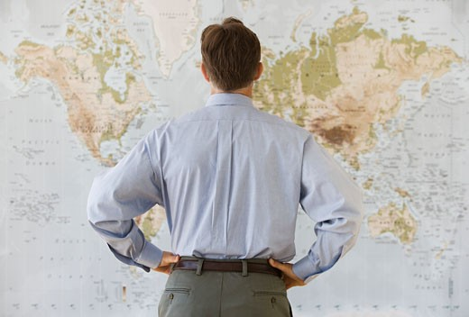 Man facing world map, rear view : Stock Photo