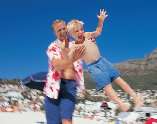 Father Swinging His Son on the Beach : Stock Photo