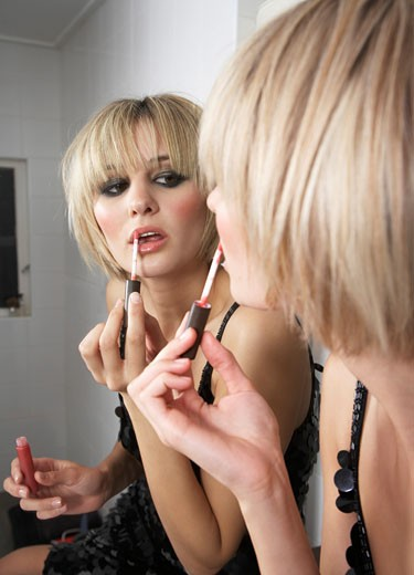 Young woman applying make-up, looking in mirror : Stock Photo