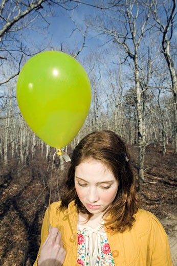 Teenage girl (16-18) walking in park holding balloon : Stock Photo