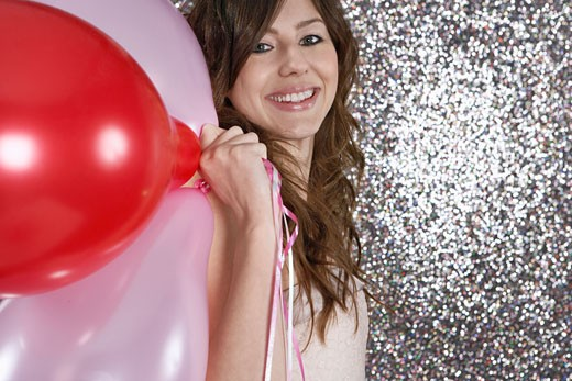 Stock Photo: 1598R-9950832 Young woman holding balloons, smiling, portrait