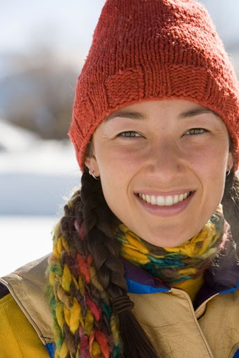 Young woman wearing knit hat and scarf, smiling, portrait : Stock Photo