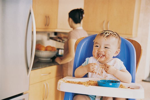 Messy Baby Sitting in a Highchair Eating Spaghetti and its Mother in the Background : Stock Photo