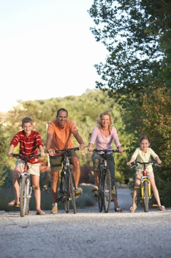 Stock Photo: 1598R-9951355 Family with daughter (7-9) and son (11-13) riding bicycles on country road, portrait