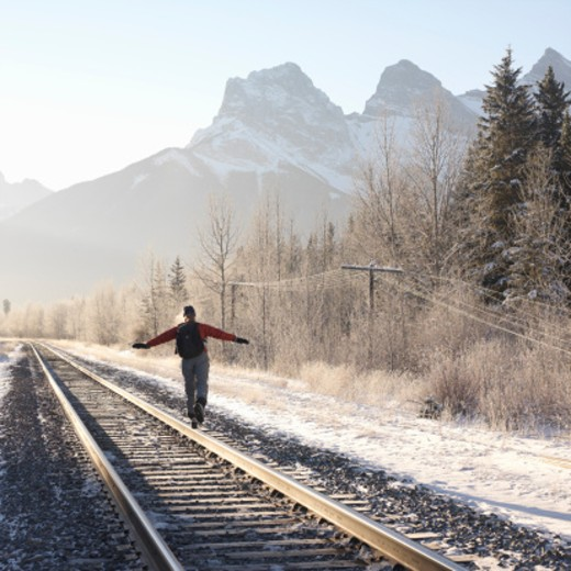 Canada, Alberta, Canmore, woman balancing on railroad track, rear view : Stock Photo
