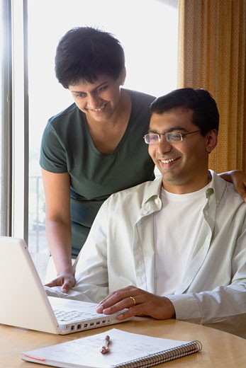 Couple looking at laptop computer in home : Stock Photo