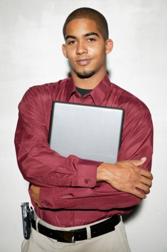 Young man embracing laptop, portrait : Stock Photo