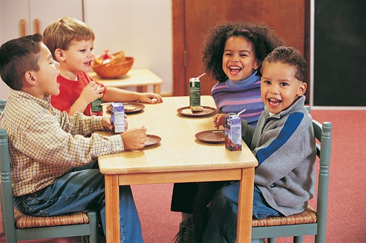 Four Nursery School Children Sitting at a Table for a Snack : Stock Photo