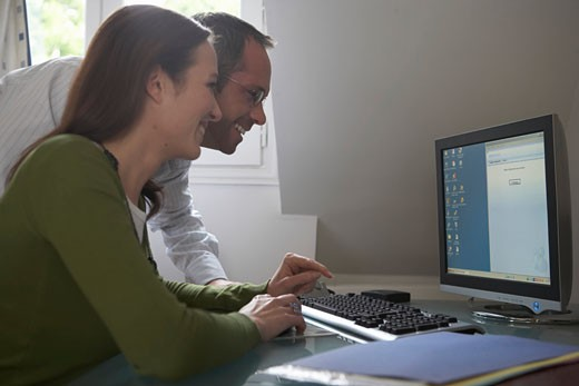 Couple using computer, smiling, side view : Stock Photo