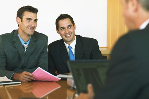 Two businessmen sitting opposite another in meeting, smiling : Stock Photo