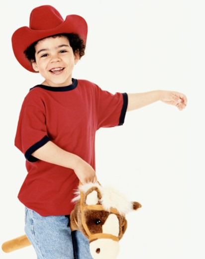 Stock Photo: 1598R-9952728 Young Boy With Cowboy Hat Riding a Toy Horse