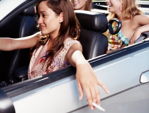 Three Teenage Girls Sit in a Convertible Car, the Driver Holding a Cigarette : Stock Photo