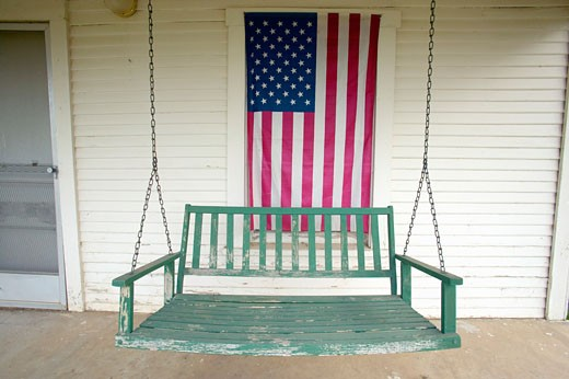 Old swing on porch displaying an American Flag and patriotic theme near Barstow CA off Route 60 : Stock Photo