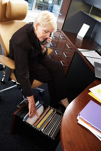 Senior businesswoman using telephone, looking in filing cabinet : Stock Photo