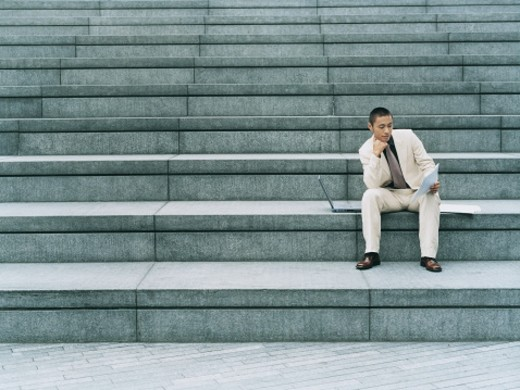 Stock Photo: 1598R-9953624 Businessman Sitting Outdoors on Steps With a Laptop Computer Reading Paperwork