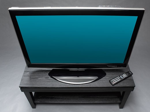 Widescreen television on table with remote control, high angle view : Stock Photo