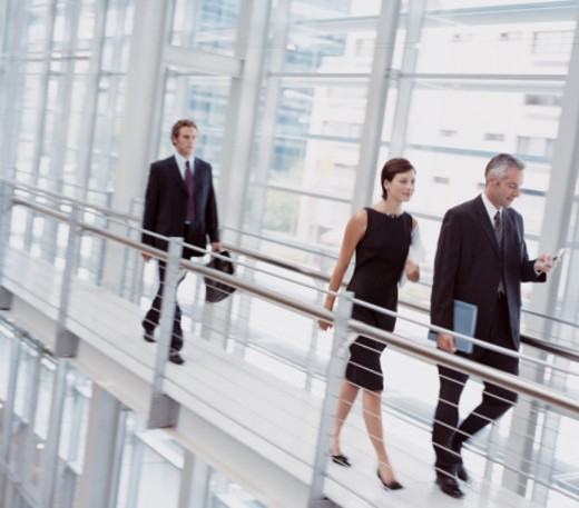 Three Business Colleagues Walking Along an Elevated Walkway in a Modern Office : Stock Photo