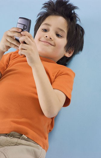 Stock Photo: 1598R-9954326 Young Boy Lying on His Back and Using a Mobile Phone
