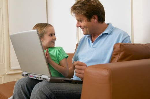 Father and daughter (5-7) on sofa with laptop, smiling : Stock Photo