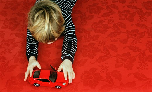 Stock Photo: 1598R-9954438 Boy (4-6) lying on stomach playing with toy car, elevated view
