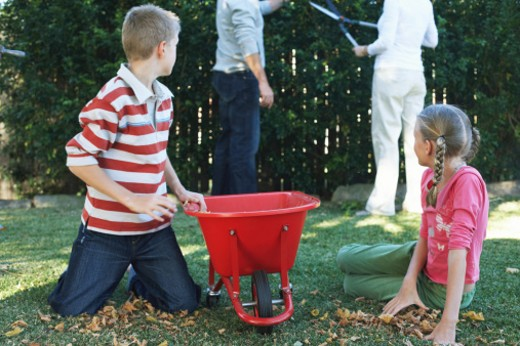 Twins (10-12) by wheelbarrow watching parents by garden hedge : Stock Photo