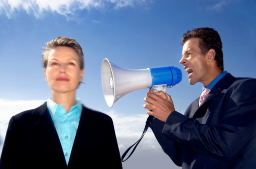 Stock Photo: 1598R-9954490 Businesswoman Ignoring a Businessman Shouting at Her Through a Megaphone