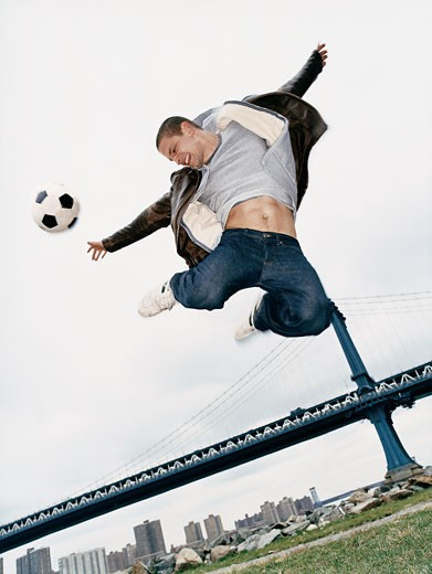 Teenage Man Jumping With a Football : Stock Photo