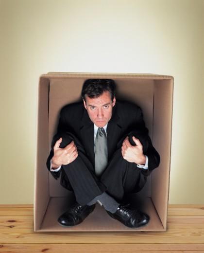 Stock Photo: 1598R-9955522 Businessman Sitting Cross Legged in a Cardboard Box
