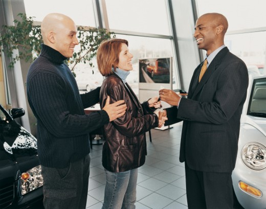 Salesman Giving a Couple Car Keys in a Car Showroom : Stock Photo