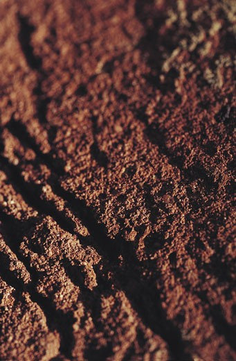 Blurred close-up of brick red dirt : Stock Photo