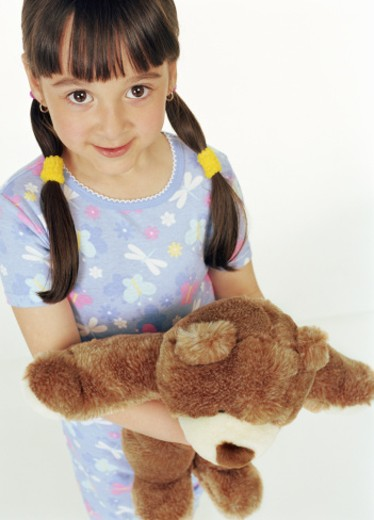 Stock Photo: 1598R-9955718 Girl (4-6) holding teddy bear, smiling, portrait