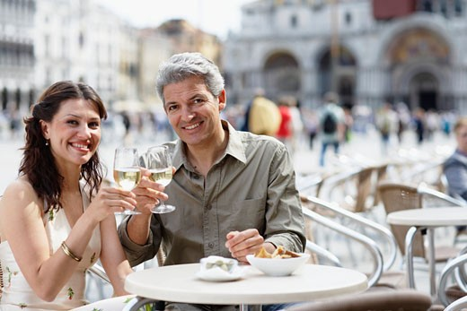 Italy, Venice, couple raising glasses at cafe table, smiling, portrait : Stock Photo
