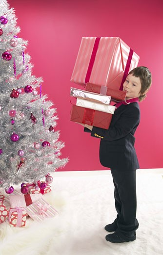 Young Boy Wearing a Suit Carrying a Stack of Christmas Presents : Stock Photo