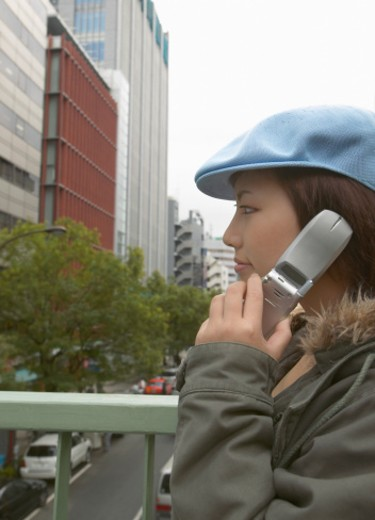 Profile of a Teenage Girl Standing on an Overpass Listening to Her Mobile Phone : Stock Photo