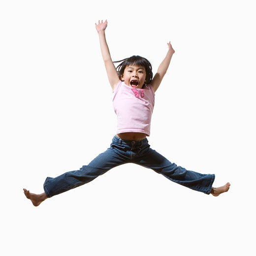 Girl (6-8) jumping in air, arms raised, portrait : Stock Photo