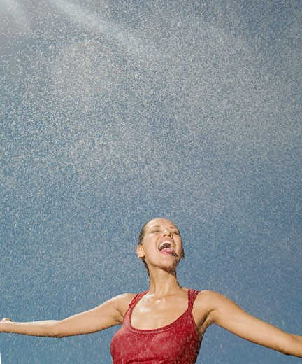 Young woman beneath spraying water : Stock Photo